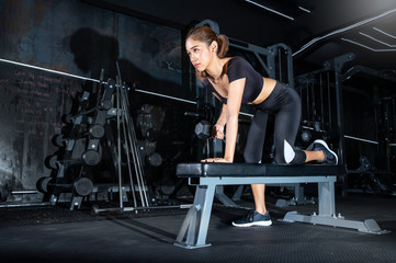 picture of fitness young woman making exercising with dumbbell at the dark gym