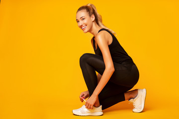 Girl Lacing Shoes Getting Ready For Workout, Yellow Background Fototapete