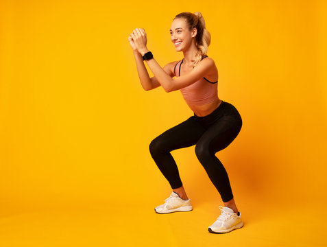 Millennial Girl Doing Deep Squat Exercise On Yellow Background