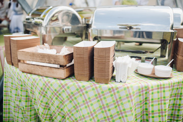 Stock photo of paper recyclable containers in stacks on the table over patterned green and white tablecloth. Box of napkins and utensils. Outdoor food festival.