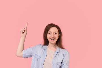 Emotional positive young woman in casual wear points finger up posing on pink background. Happy woman advertises personal offer and discount in the online store. Place for text