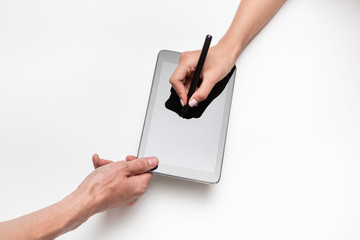 Close up top view of male and female hands holding tablet. Man signs contract with a pen using digital tablet. Concept of strong business relationships and partnership. Successful deal.