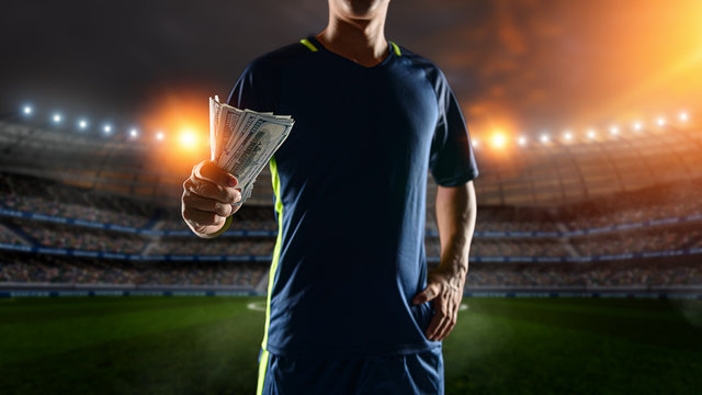 Soccer players holding large amount of bills at Soccer stadium in background