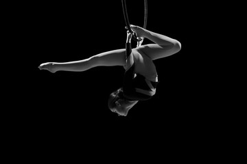 A female gymnast performing exercises on an air ring (hoop)