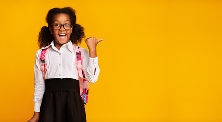 Elementary Student Girl Pointing Thumbs At Copy Space, Yellow Background