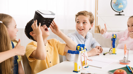 Schoolboy playing with vr glasses in classroom