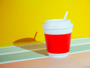 Wall Mural - Red coffee cup with shadow yellow background.Modern concept
