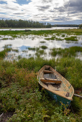 Shabby semi-flooded boat on the bank of the picturesque Kalix River in Northern Sweden