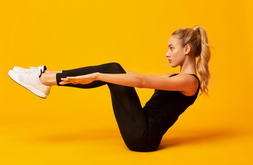 Girl Doing Abs Exercise With Leg Raise On Yellow Background Fototapete