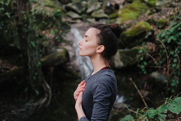 Young woman practicing breathing yoga pranayama outdoors in moss forest on background of waterfall. Unity with nature concept.