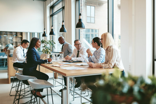Diverse businesspeople smiling and talking together at an office