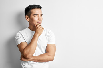 Portrait of smart thinking Kazakh man dressed in casual on white background. Asian handsome student in studio