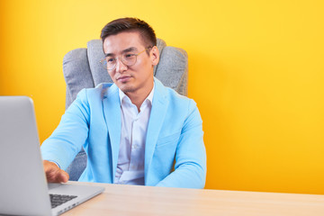 Asian Kazakh businessman in a suit and glasses with a laptop computer works in the office, a successful professional manager solves business issues