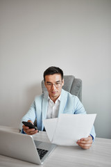 Asian Kazakh businessman in a suit and glasses with a laptop computer in the office speaks by mobile phone, solves business issues, negotiates a deal.