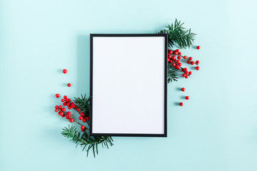 Christmas modern composition. Photo frame, red berries on pastel blue background. Christmas, New Year, winter concept. Flat lay, top view, copy space