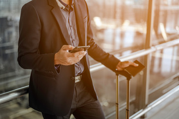 Businessman using mobile phone at the airport. holding passport with luggage.Travel and business airport concept. Fototapete