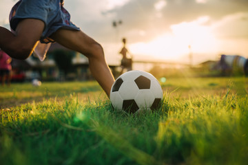 A boy kicking a ball with bare foot while playing street soccer football on the green grass field for exercise in community rural area under the twilight sunset.