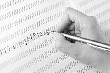 Hand writing music notes close-up in black and white