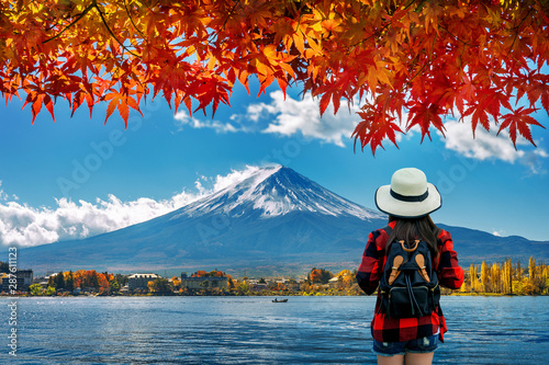 Wall mural Woman traveler with backpack looking to Fuji mountains in Autumn, Japan.