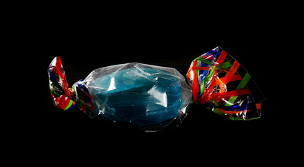 Colorful candies with transparent cellophane wrapping isolated on black background