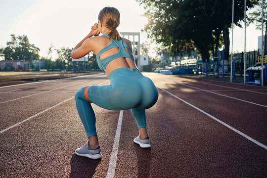 Back side view of attractive athlete girl in stylish sportswear squatting with rubber band on stadium