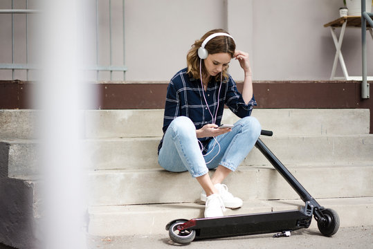 Young woman with electric scooter, sitting on stairs, listening music