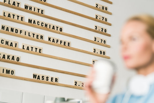 Price board in a coffee shop with customer carrying cup of coffee