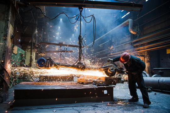 Employee grinding steel with sparks - focus on grinder. Steel factory.