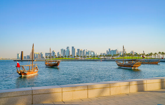 Four dhow moored in bay with Museum Islamic Arts building in background.