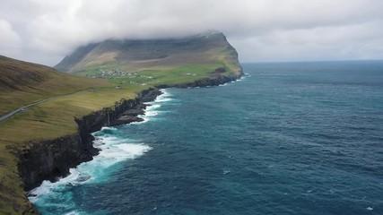 Wall Mural - Flight over a coastline towards the village of Vidareidi on Faroe Islands