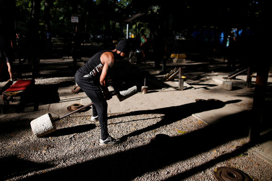 A man lifts weights made of cement in a handmade gym made with construction bars, rusty car parts, and other recycled materials in Caracas