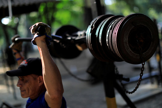 A man lifts weights made of rusty car parts in a handmade gym made with construction bars, cement, and other recycled materials in Caracas