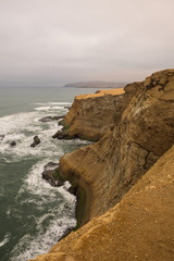 Dramatic coastline with intense colors in the desert of Paracas National Reserve, Peru
