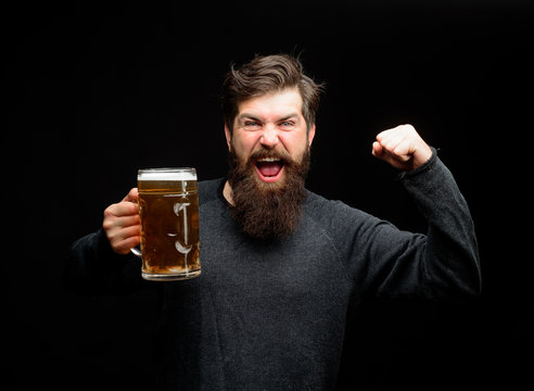 Bearded man drinking beer from glass at bar or pub. Drinks, alcohol, leisure and people concept. Bad habits. Bearded drunk hipster male holds craft beer. Stylish man with beard holds mug of beer.