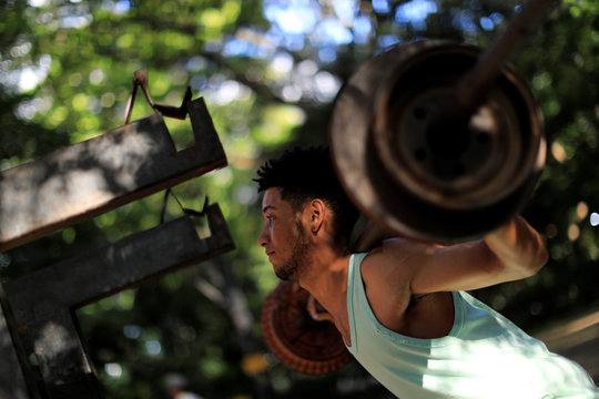 A man lifts weights in a handmade gym made with construction bars, cement, and other recycled materials in Caracas