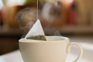 hand putting a pyramid tea bag in a hot water cup in the morning