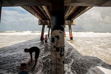 Children play under the pier at Jacksonville Beach ahead of Hurricane Dorian in Jacksonville