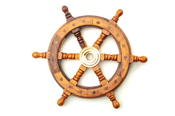Navigation, nostalgia for bygone age of discovery and leadership conceptual idea with vintage ship steering wheel rudder made of wood and brass isolated on white background with clipping path cutout