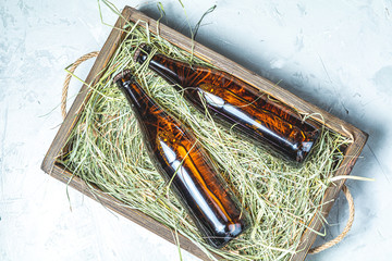 Craft beer with dried grass in wooden box on gray concrete surface