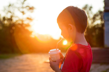 Kid boy drinks cocoa or soda in a cup with tube on sunset background. Silhouette of a drinking boy at sunset