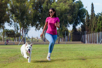 Sporty woman and dog running together in the park on summer sunset. Cheerful female athlete training and exercising outdoor with her pet.