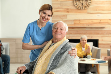 Nurse covering elderly man with blanket at retirement home. Assisting senior people
