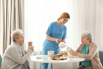 Nurse assisting while elderly women having breakfast at retirement home