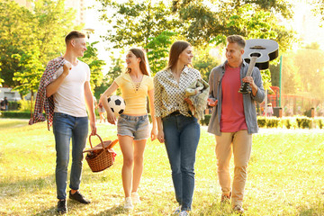 Young people with picnic basket in park on summer day