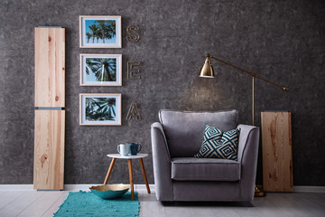 Interior of modern room with pictures on grey wall and cozy armchair