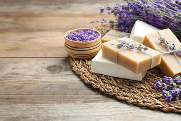 Wall Mural - Handmade soap bars with lavender flowers on brown wooden table. Space for text