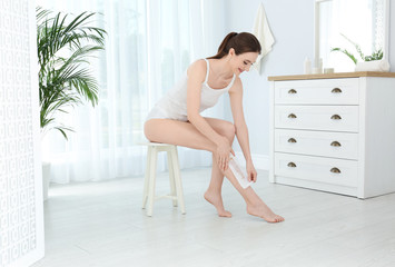 Young woman doing leg epilation procedure with wax strips at home