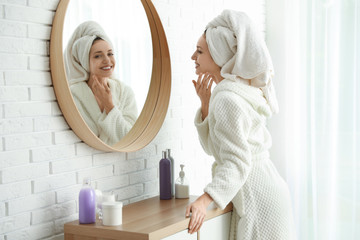 Pretty young woman with towel on head near mirror indoors