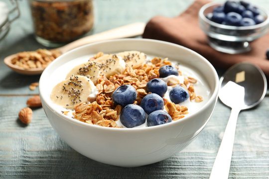Bowl of yogurt with blueberries, banana and oatmeal on color wooden table
