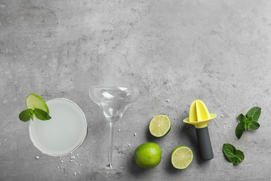 Flat lay composition with tasty refreshing cocktail on grey background. Space for text